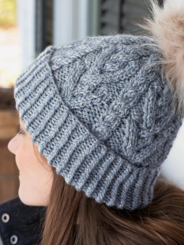 Cabled hat Portage with a pompom. Free knitting pattern.