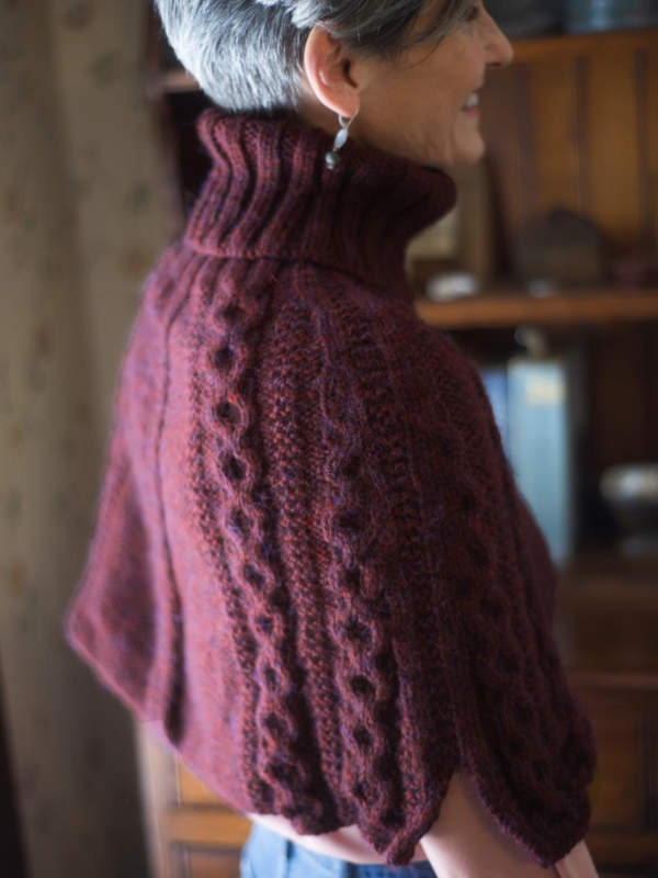 Cozy cabled capelet Barachois with a turtleneck. Free knitting pattern.