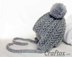 Knitting winter (warm) hat with pom poms for child. Left view.