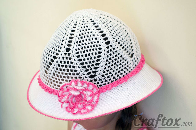 Сrochet white hat for 4-5-year-old girl. Left view with flower and edging according